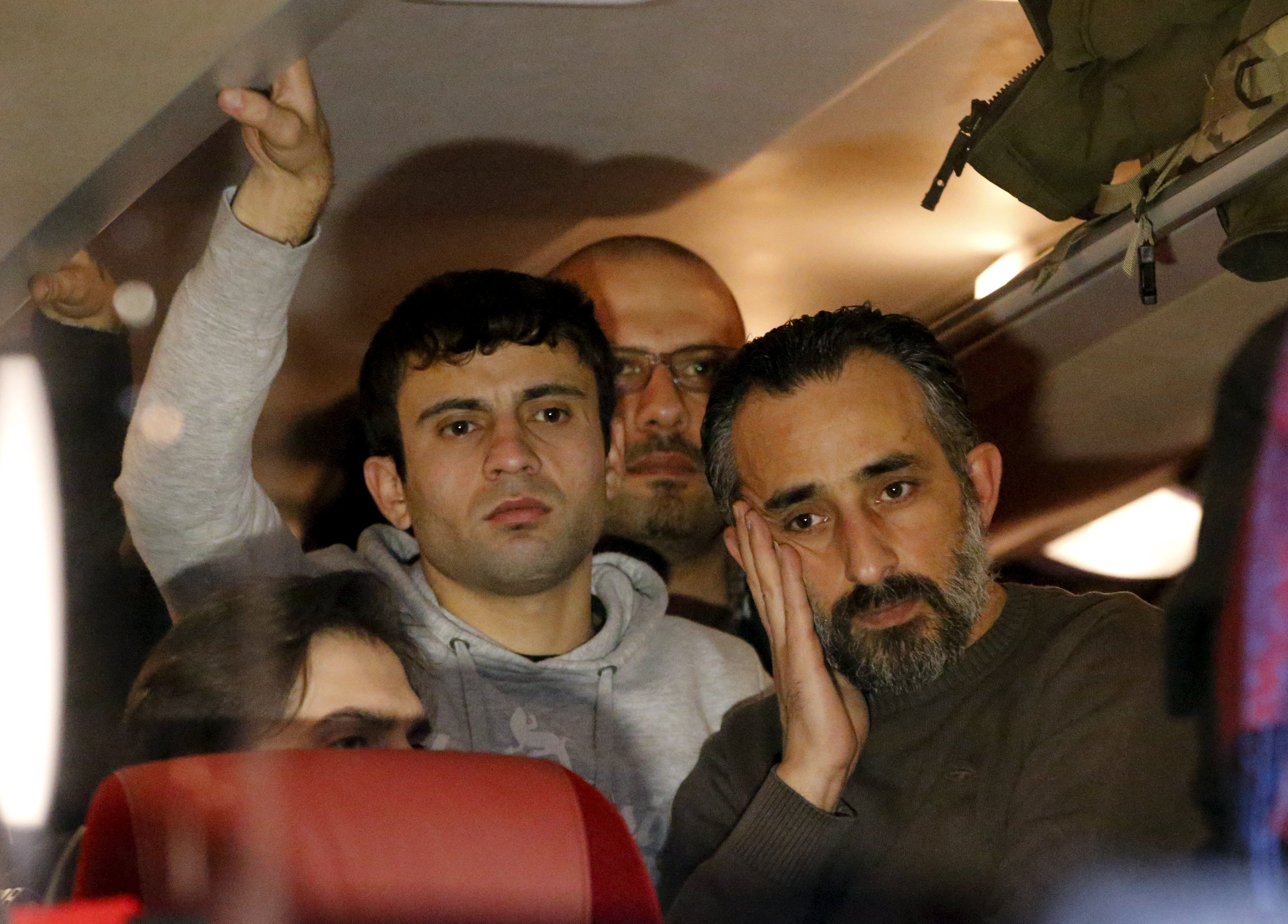 Refugees stand inside a bus arriving from the Bavarian town of Landshut to the Chancellery building in Berlin, Germany, January 14, 2016