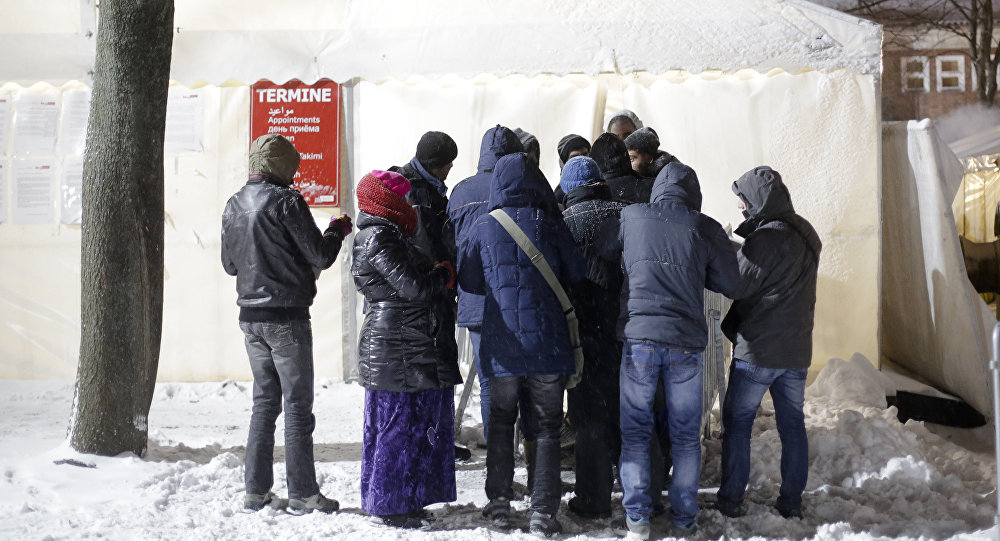 Migrants line up for an appointment in front of a waiting tent on a cold and snowy early morning, at the central registration center for refugees and asylum seekers LaGeSo (Landesamt fuer Gesundheit und Soziales - State Office for Health and Social Affairs) in Berlin