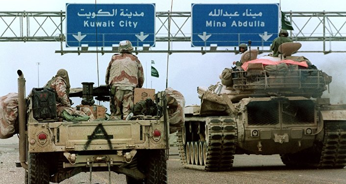 A US Hummvee jeep (l) and a Saudi tank pass under a highway sign directing them to Kuwait City 26 February 1991 during Desert Storm Allied forces offensive