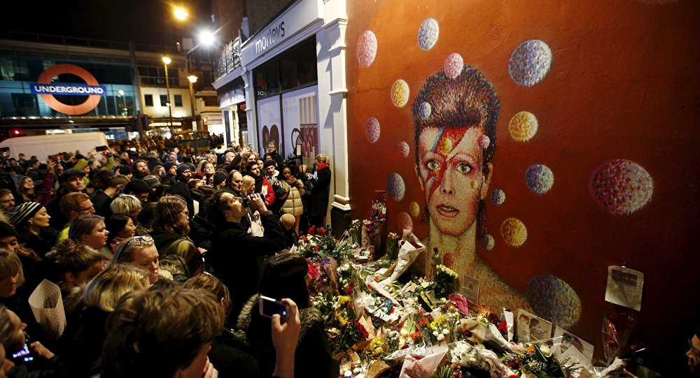 Fans stand by floral tributes at a mural of David Bowie in Brixton, south London, Britain January 11, 2016