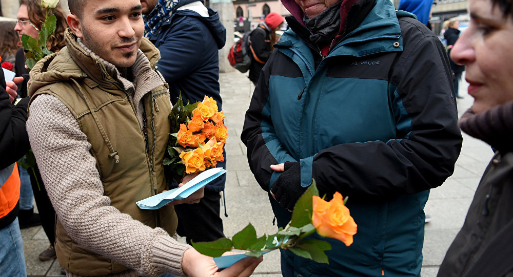 Refugees from Syria present flowers to passers-by as they demonstrate against violence near the Cologne main train station in Cologne, western Germany on January 16, 2016, where hundreds of women were groped and robbed in a throng of mostly Arab and North African men during New Year's festivities