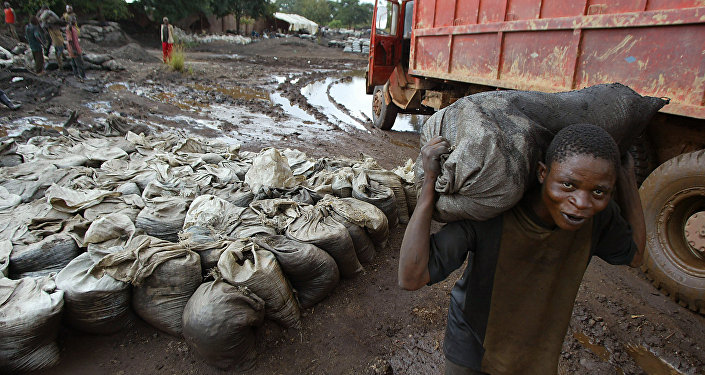 A young man carries wet cobalt on his back at the Shinkolobwe mine 35km from the town of Likasi, Democratic Republic of Congo, in this Saturday, April 10, 2004.