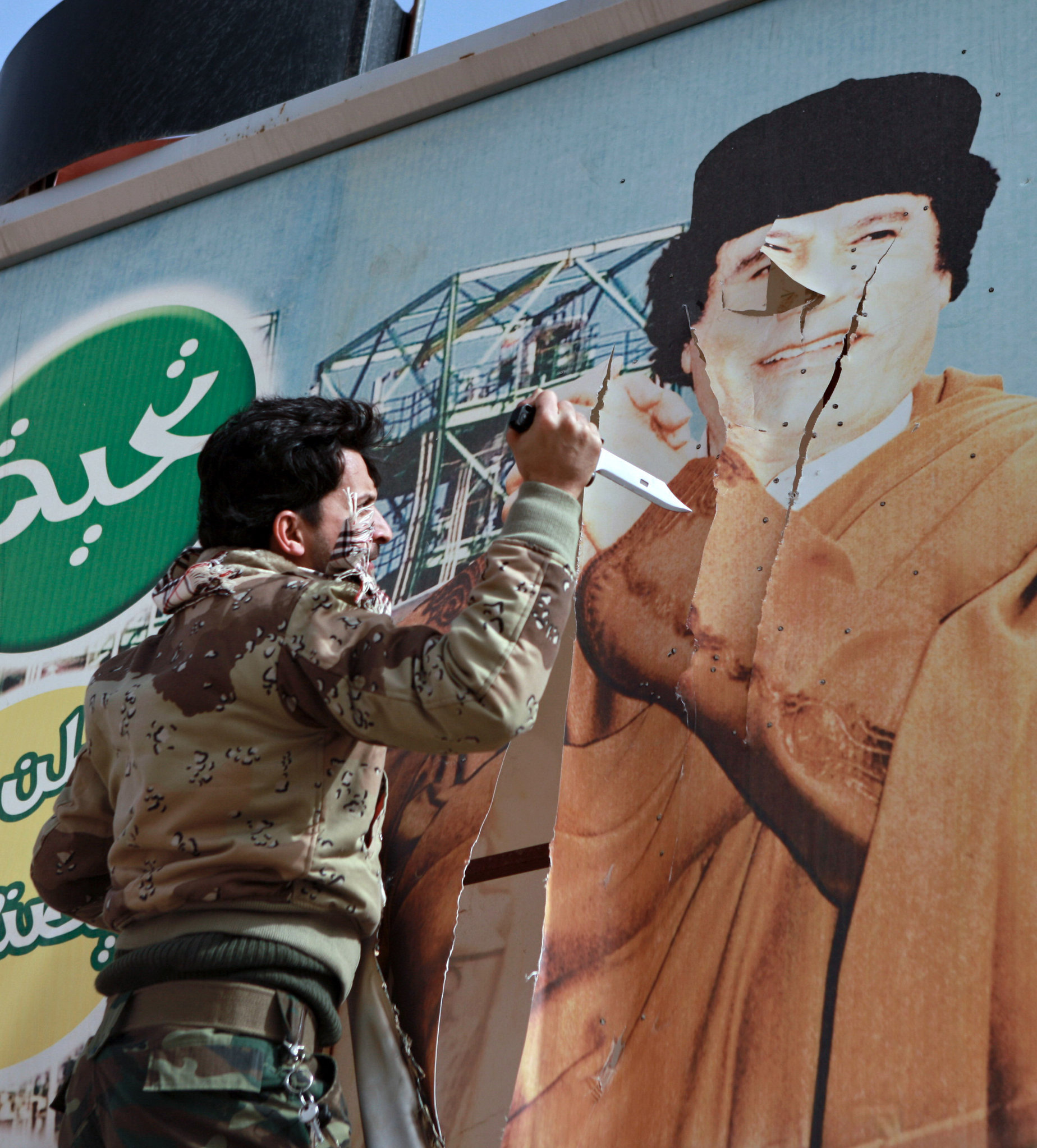 Libyan opposition supporter uses knife to cut a poster of Muammar Gaddafi in the captured rebel town of Ras Lanuf in the east of the country