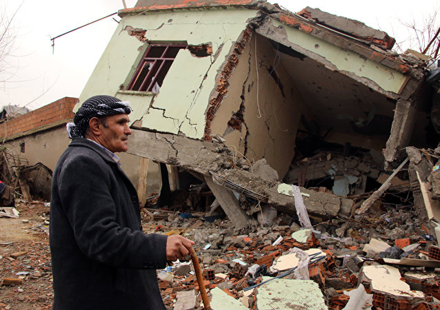 A resident walks on the rubble of a destroyed house in the mostly-Kurdish town of Silopi, in southeastern Turkey.