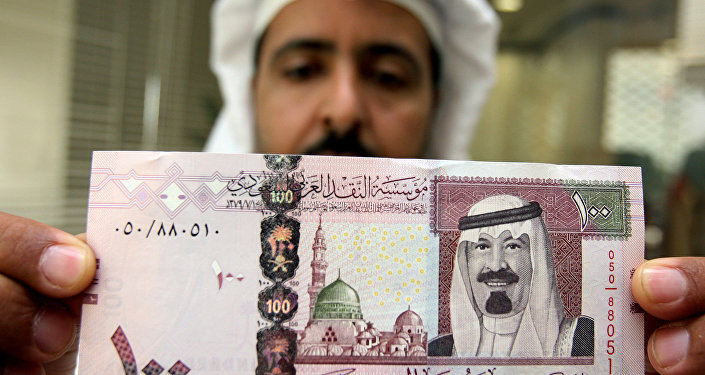 A Saudi banker displays the new one hundred riyal banknote bearing the portrait of Saudi King Abdullah bin Abdul Aziz al-Saud at a bank in Riyadh, 05 June 2007