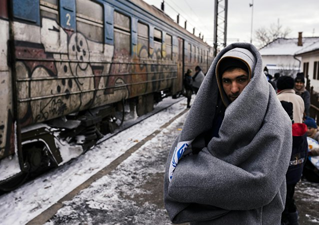 A migrant wrapped in a blanket to keep warm, waits with other migrants and refugees to board a train heading to the border with Croatia at the train station in Presevo, on January 19, 2016, after crossing the Macedonian border into Serbia