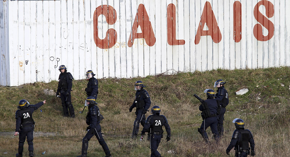 Police officers look for migrants attempting to access the Channel Tunnel in Calais, northern France, Thursday, Jan.21, 2016