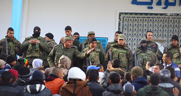 An army soldier tries to disperse protesters as he stands guard with his comrades outside the local government office during a protest in Kasserine, Tunisia January 22, 2016.