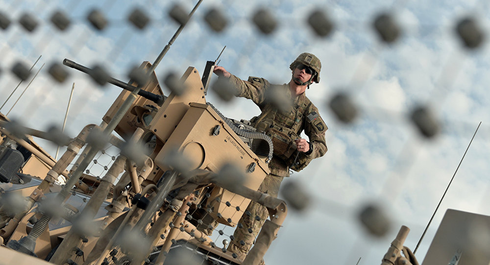 A US soldier of the second Platoon Bravo Company, 1-3271 Infantry of Combined Team Bastogne (Nangarhar), 1st Brigade Combat Team, 101st Airborne Division (Air Assault) loads a machine gun on a manned turret over a mine resistant all-terrain vehicle