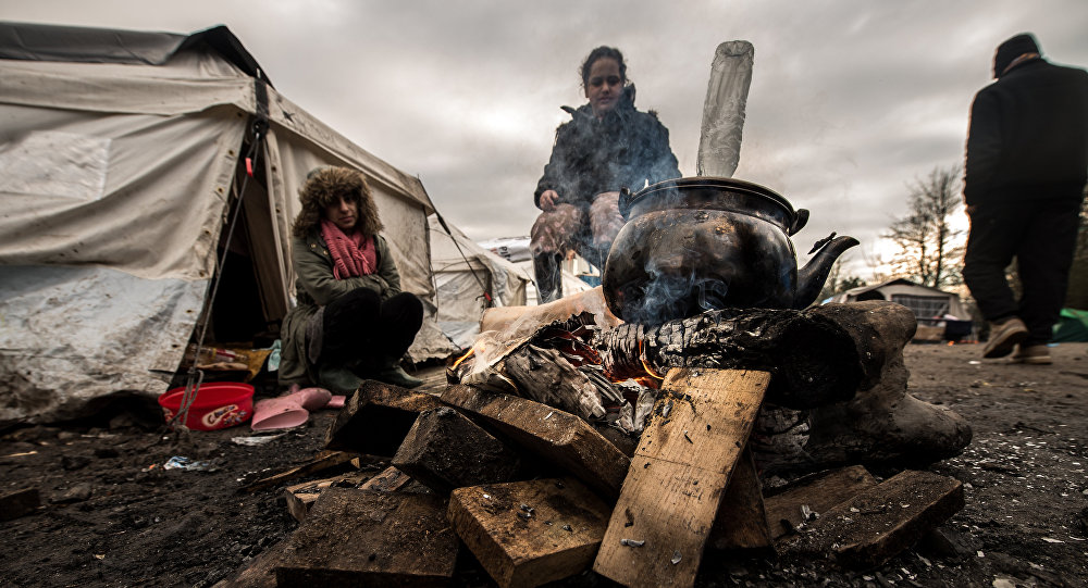 Migrants get warm around a brazier in the migrants camp of Grande-Synthe, near Dunkirk