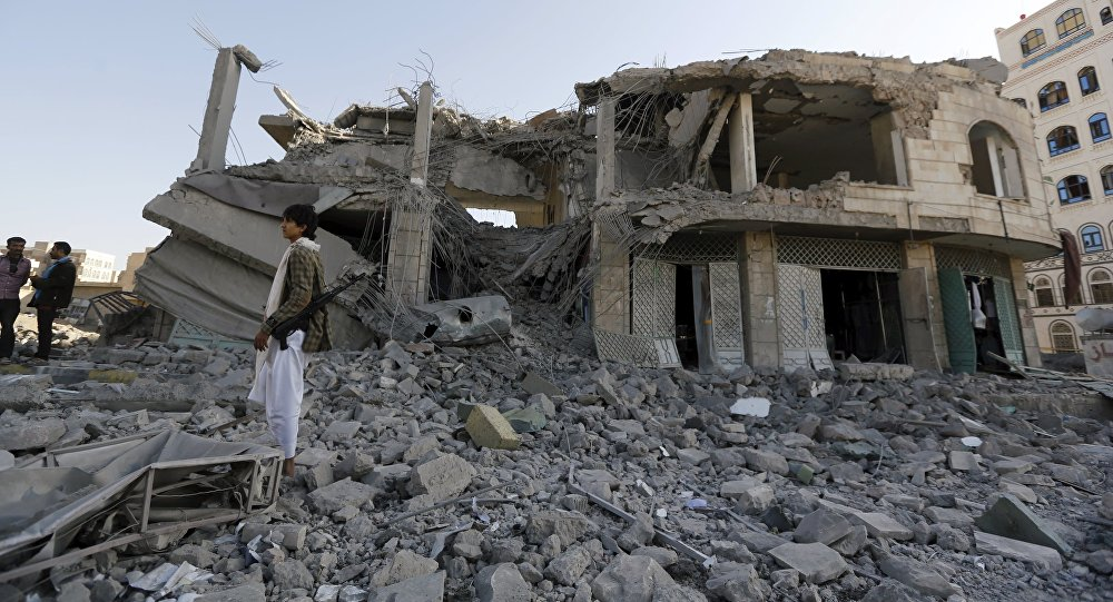 Houthi militant stands guard outside the house of court judge Yahya Rubaid after a Saudi-led air strike destroyed it, killing him, his wife and five other family members, in Yemen's capital Sanaa January 25, 2016.