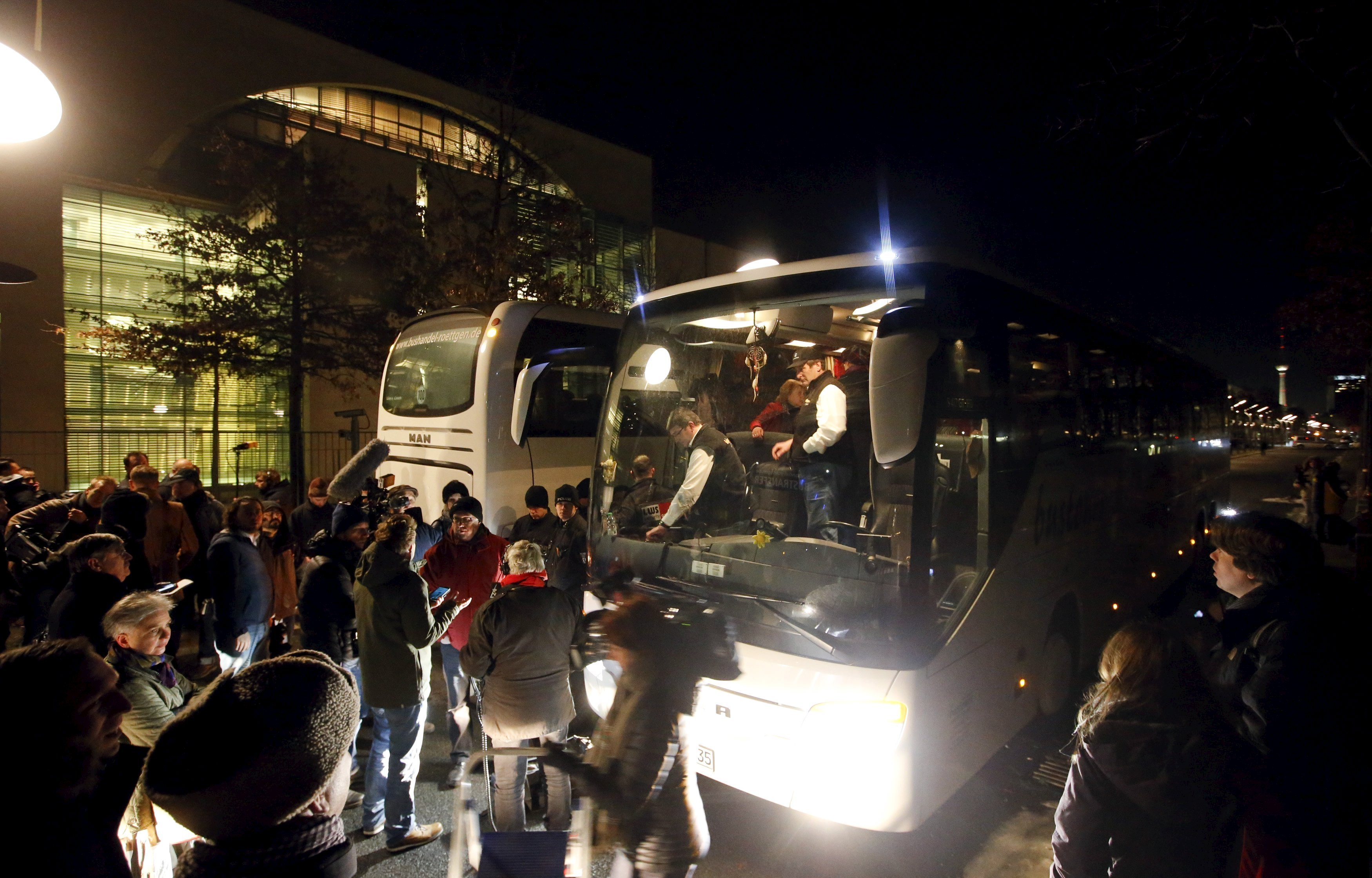 A bus (R) with refugees from the Bavarian town of Landshut is pictured after its arrival to the Chancellery building in Berlin, Germany, January 14, 2016