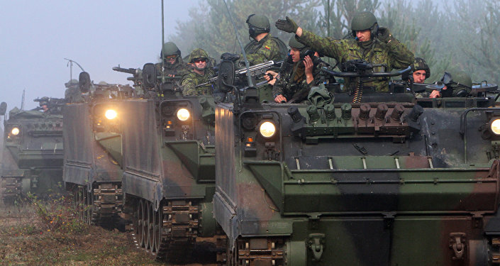 Soldiers ride in tanks during the multinational military exercise for Lithuanian, Polish and Ukrainian troops, Maple Arch 2012, at Pabrade Training Area in Lithuania's Svencionys district, near Vilnius, on September 21, 2012