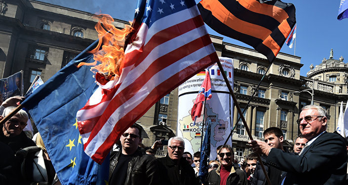 Serbian nationalist politician Vojislav Seselj (R) surrounded by his supporters holds a burning NATO flag during an anti-government rally on March 24, 2015, in front of the building of the former federal Interior Ministry in Belgrade