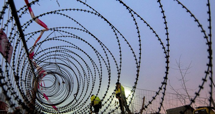 Workers take measurements of a near finished section of a 3,7 km long fence at a border crossing between Austria and Slovenia at Spielfeld, Austria on December 9, 2015.