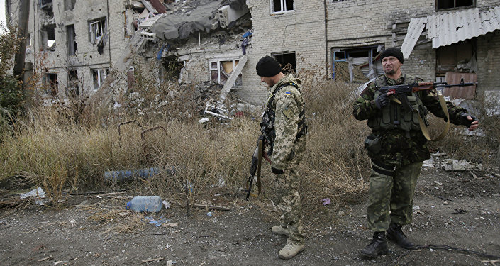 Ukrainian servicemen walks in the yard of a destroyed building in the Pisky village near Donetsk on October 26, 2015