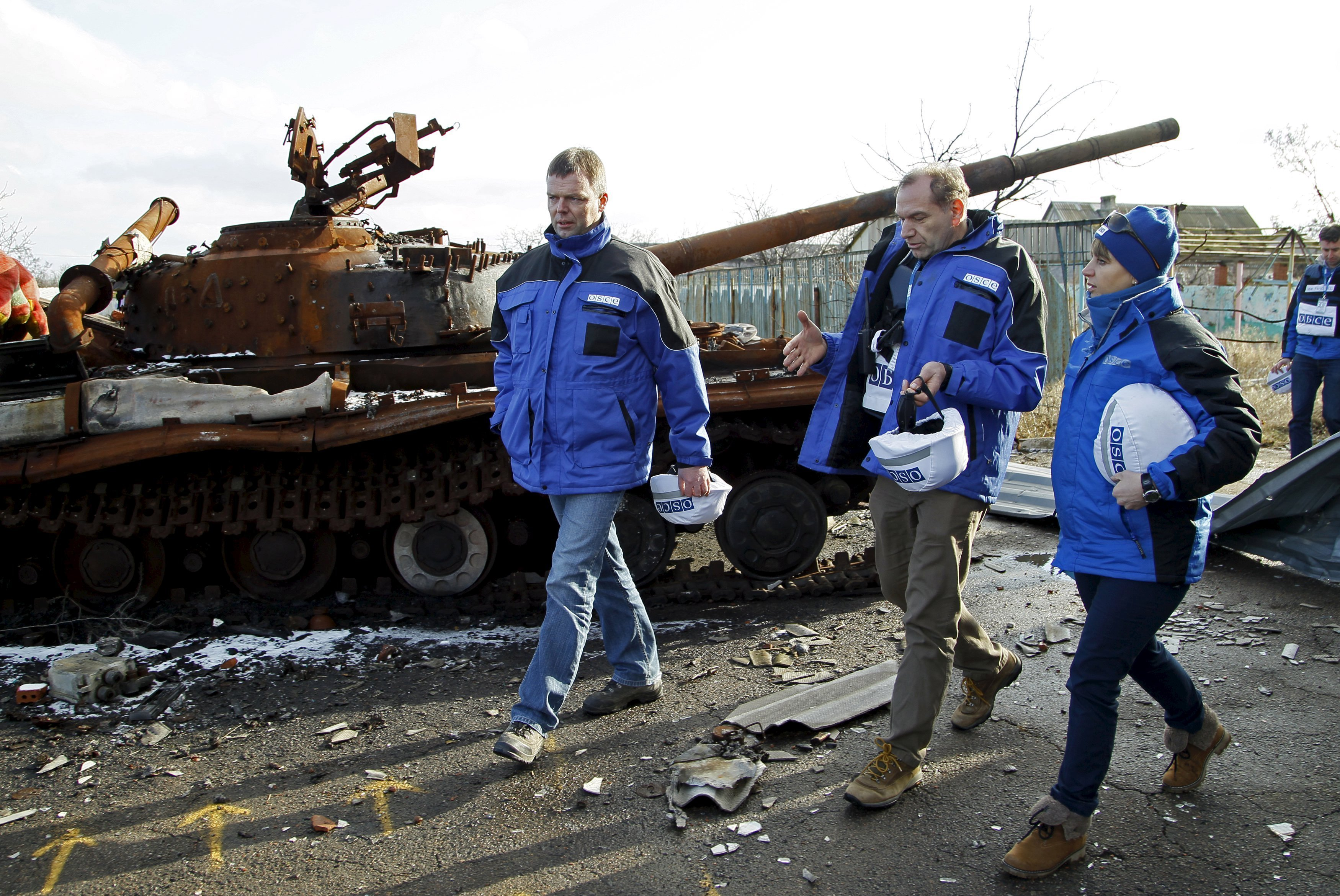 Deputy Chief of the OSCE's Special Monitoring Mission to Ukraine Alexander Hug (L), with members of the mission, walks past a burnt tank as he inspects an area between DPR forces and Ukrainian government troops in the village of Kominternove north-east of the port city of Mariupol, Ukraine, January 15, 2016