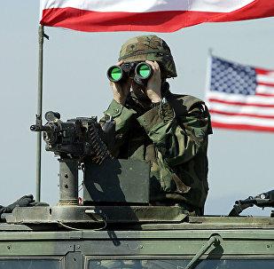 A US soldier peers through binoculars