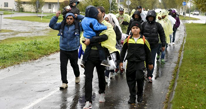 Refugees walk through the pouring rain from a public transport centre to the Lappia-building refugee reception centre in Tornio, northwestern Finland, on September 2015