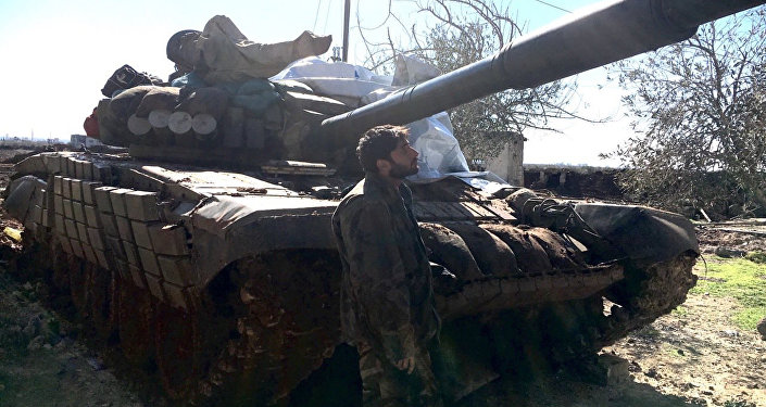 Syrian Arab Army soldier stands near a T72 tank in the town of Al-Shaykh Maskin in the Daraa province liberated from terrorists