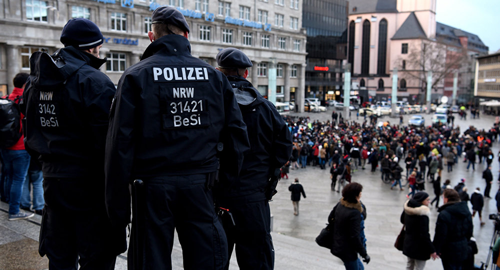 Policemen look on as refugees from Syria demonstrate against violence near the Cologne main train station in Cologne, western Germany on January 16, 2016