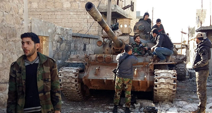 Government forces chat near a tank three kilometres from the Shiite villages of Nabbul and Zahra in Syria's northern Aleppo province which have been under siege by the Islamic State (IS) group for three years on February 2, 2016