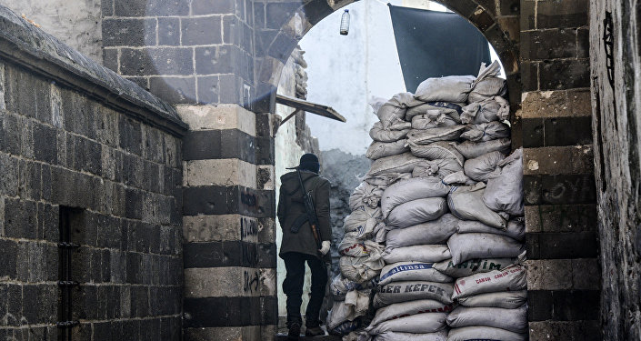 Kurdish fighter walks through barricads in the Sur district in Diyarbakir on December 11, 2015
