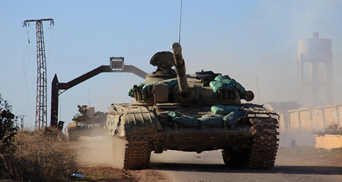 Syrian government forces' tanks drive in the village of Tal Jabin, north of the embattled city of Aleppo