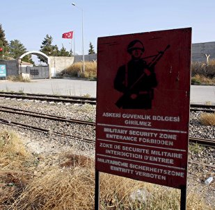 A Turkish military warning sign, with the closed Karkamis border gate in the background, is pictured in Karkamis, bordering with the Islamic State-held Syrian town of Jarablus, in Gaziantep province, Turkey, in this August 1, 2015 file photo