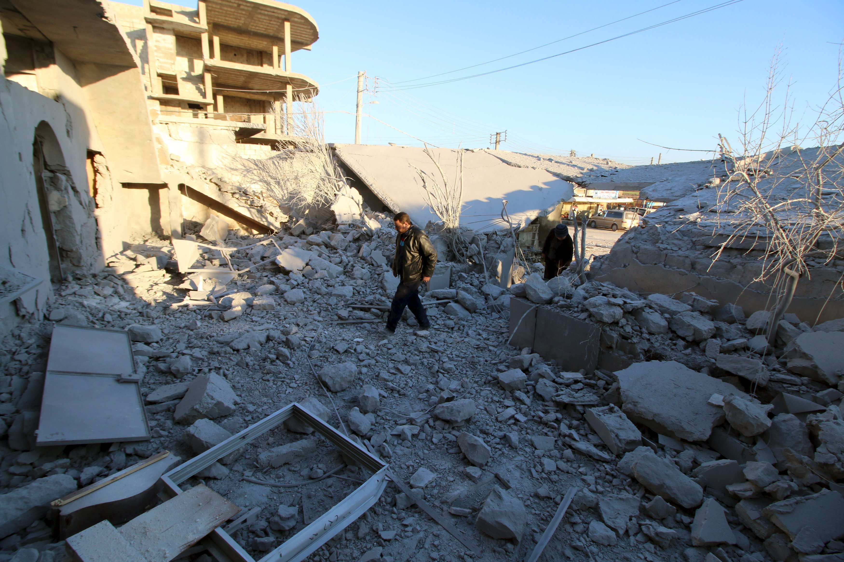 Residents inspect damage after airstrikes by pro-Syrian government forces in Anadan city, about 10 kilometers away from the towns of Nubul and Zahraa, Northern Aleppo countryside, Syria February 3, 2016