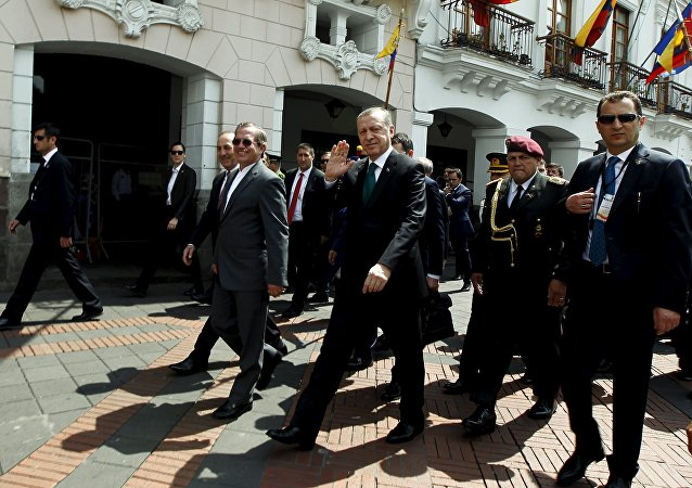 Turkish President Tayyip Erdogan waves next to Ecuador's Foreign Affairs Ricardo Patino while walking into Carondelet Palace in Quito, Ecuador, February 4, 2016