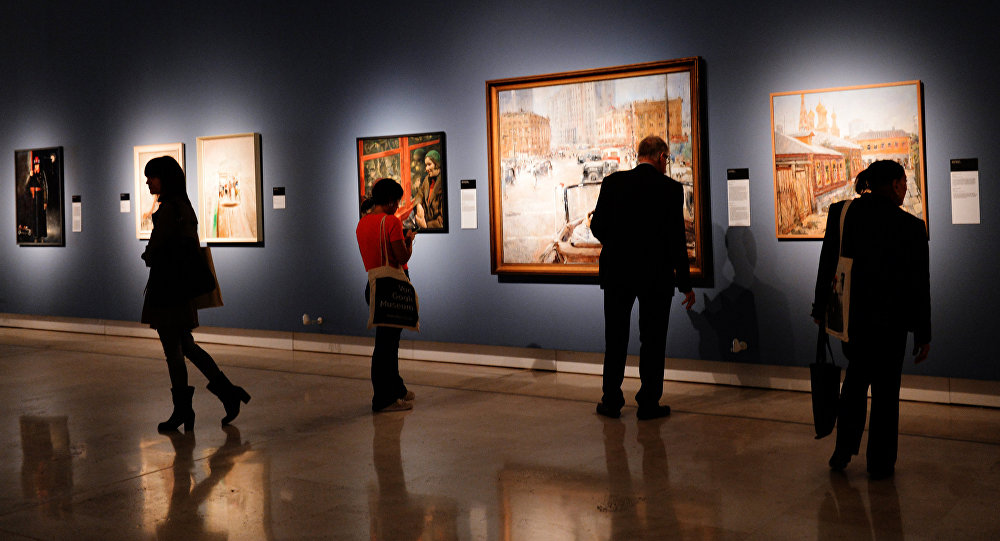 Visitors at the Palazzo delle Esposizioni in Rome attend an exhibition of paintings from the collection of the Institute for Russian Realist Art (IRRA), state-owned museums and private collections called 'Russia on the Road (1920-1990).' Center: The New Moscow by Yury Pimenov, courtesy of the State Tretyakov Gallery