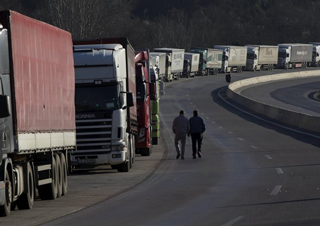 Truck drivers walk next to parked trucks as protesting farmers (not pictured) block the road leading to the border station of Greece with Bulgaria during a demonstration against planned pension reforms near the Greek village of Promachonas.
