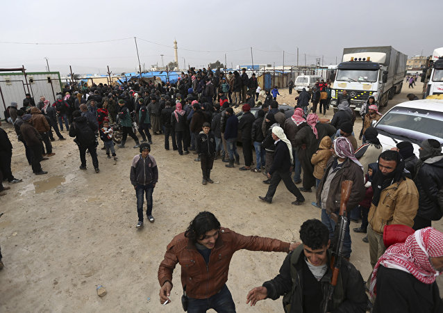 Syrians gather at the Bab al-Salam border gate with Turkey, in Syria, Saturday, Feb. 6, 2016
