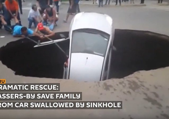 Family rescued after car swallowed by giant sinkhole