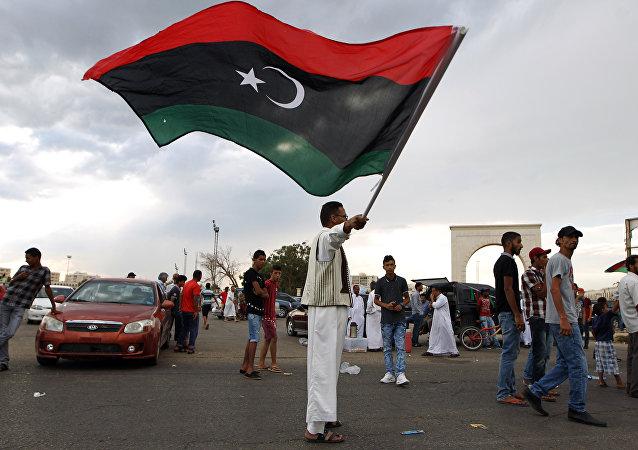 A Libyan man waves his national flag