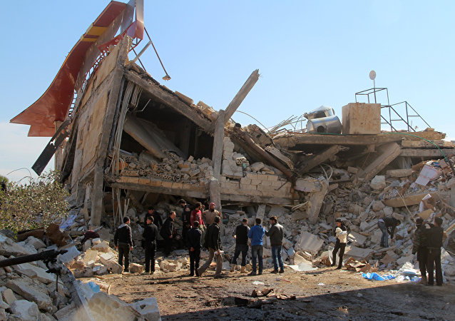 People gather around the rubble of a hospital supported by Doctors Without Borders (MSF) near Maaret al-Numan, in Syria's northern province of Idlib, on February 15, 2016