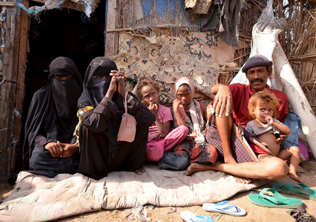 A family poses for a photo in their hut in a slum neighborhood in Yemen's Red Sea city of Houdieda, February 15, 2016.