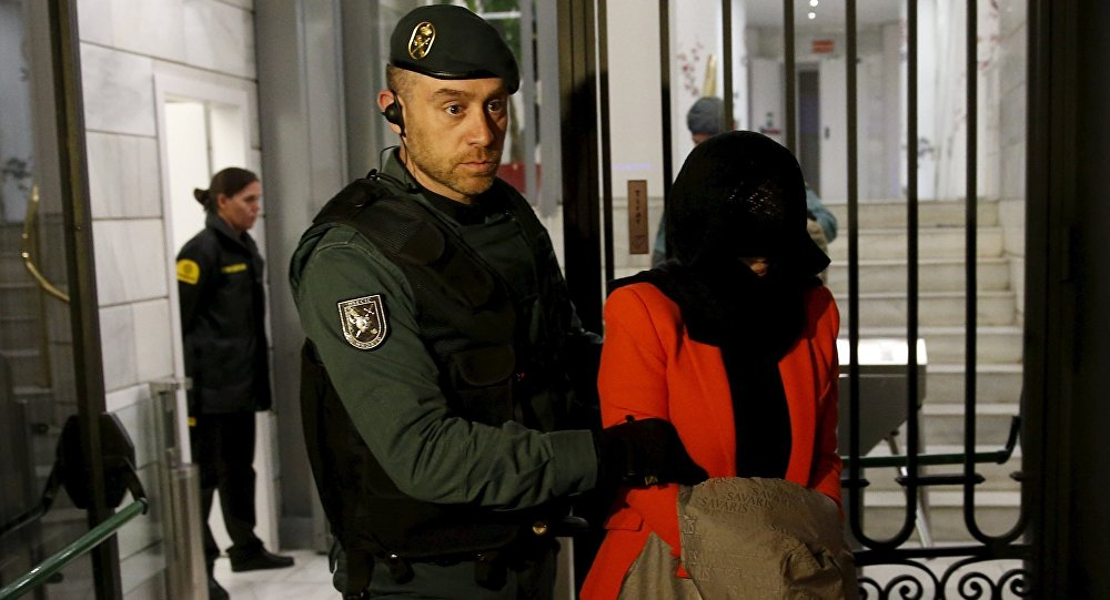 A suspect is led by a Spanish Civil Guard officer as they leave the headquarters of Industrial and Commercial Bank of China (ICBC) during a raid in Madrid, Spain, February 17, 2016