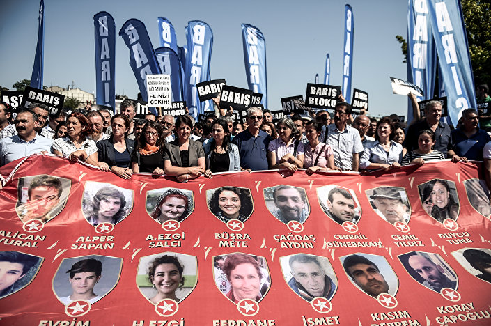 Protesters and members of Turkey's People's Democracy Party (HDP) hold a banner with pictures of the victims of the Suruc bomb attack after their peace march was banned by authorities in the Aksaray district of Istanbul on July 26.