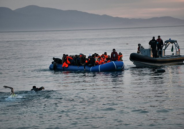 Refugees and migrants massed onto an inflatable boat reach Mytilene, northern island of Lesbos, after crossing the Aegean sea from Turkey on February 17, 2016