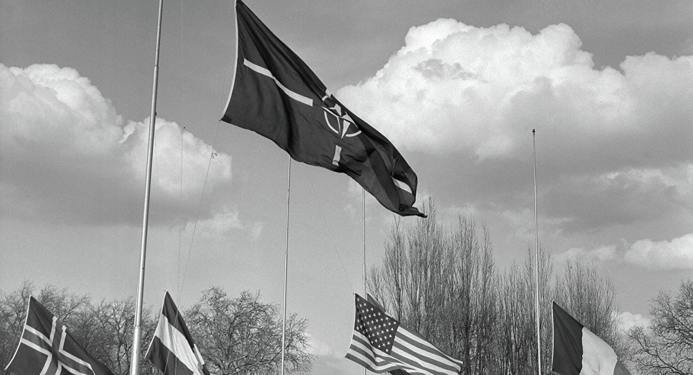 Soldiers hoist the flags of the members countries of the Atlantic Alliance (NATO) during the farewell ceremony at the SHAPE (Supreme Headquarters Allied Powers Europe) in Rocquencourt, Paris suburb, on March 31, 1967.