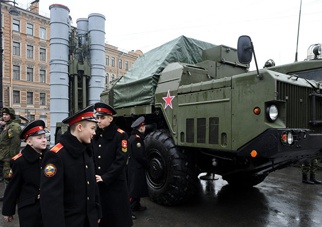 Cadets walk close to a Russian surface-to-air missile system S-300 PMU during a military exhibition marking the upcoming Defenders of the Fatherland Day holiday in Saint Petersburg on February 20, 2015