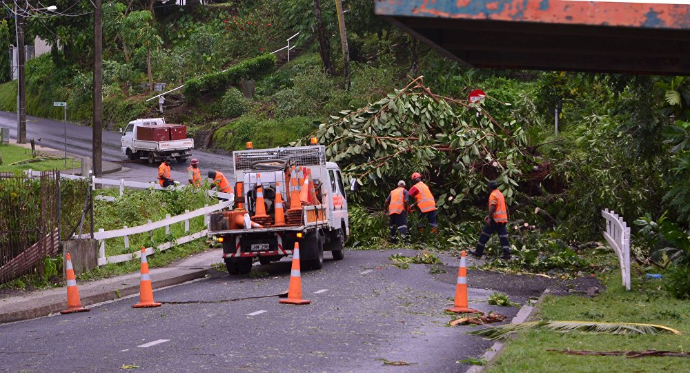 City workers clear fallen trees from a road in Fiji's capital Suva after Cyclone Winston swept across Viti Levu Island, February 21, 2016.