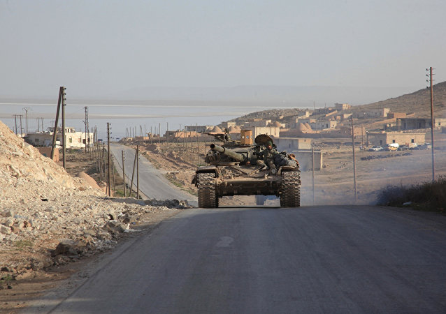 Syrian government forces drive a tank on a road during a military operation against Daesh in the villages of Zarour and Khanaser, in the Aleppo province, on February 26, 2016