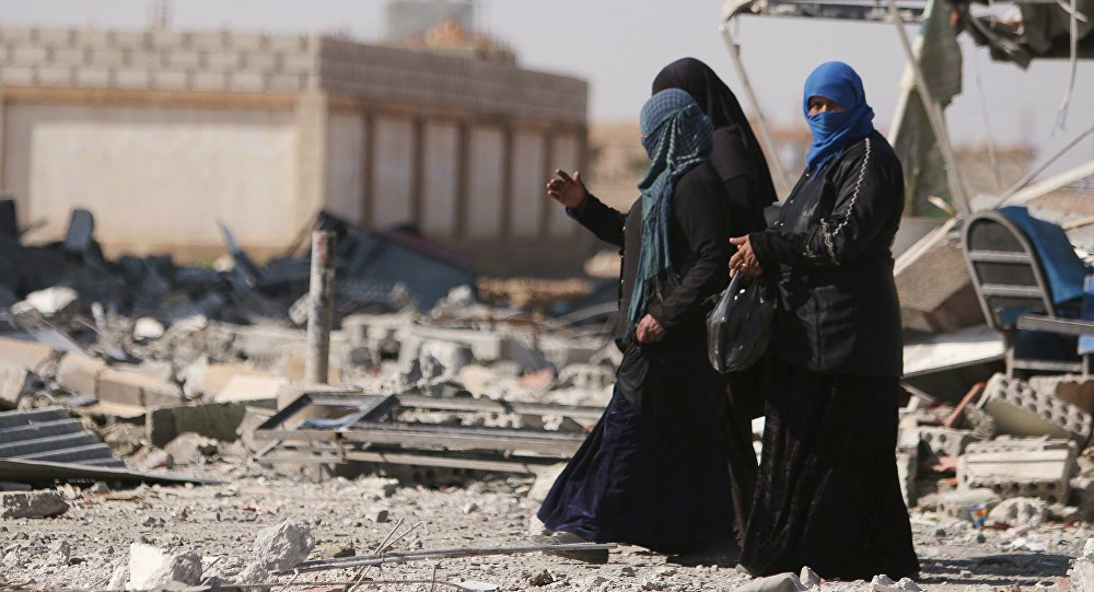 Women walk on rubble in al-Shadadi town, in Hasaka province, Syria February 26, 2016