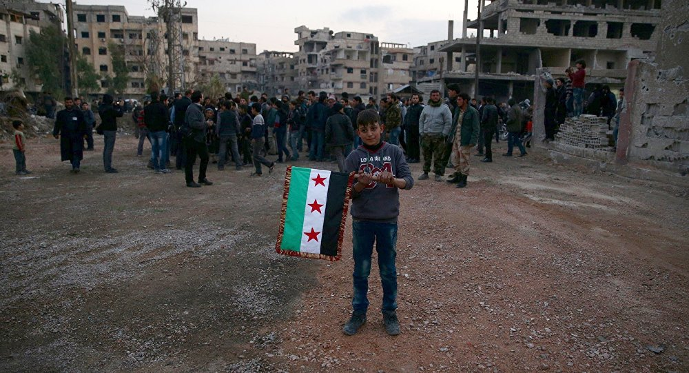 A boy carries an opposition flag as rebel fighters and civilians gather during the arrival of an aid convoy of Syrian Arab Red Crescent and United Nation (UN) to the rebel held besieged town of Kafr Batna, on the outskirts of Damascus, Syria February 23, 2016