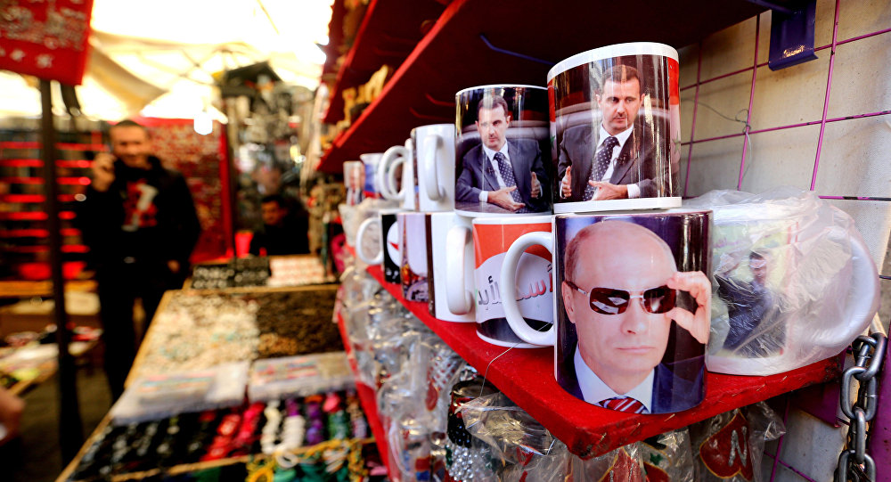 A Syrian vendor sells mugs bearing portraits of Russian President Vladimir Putin (bottom) and Syrian President Bashar Assad (top) in the popular Hamidiyeh market in the old part of the capital Damascus on November 26, 2015
