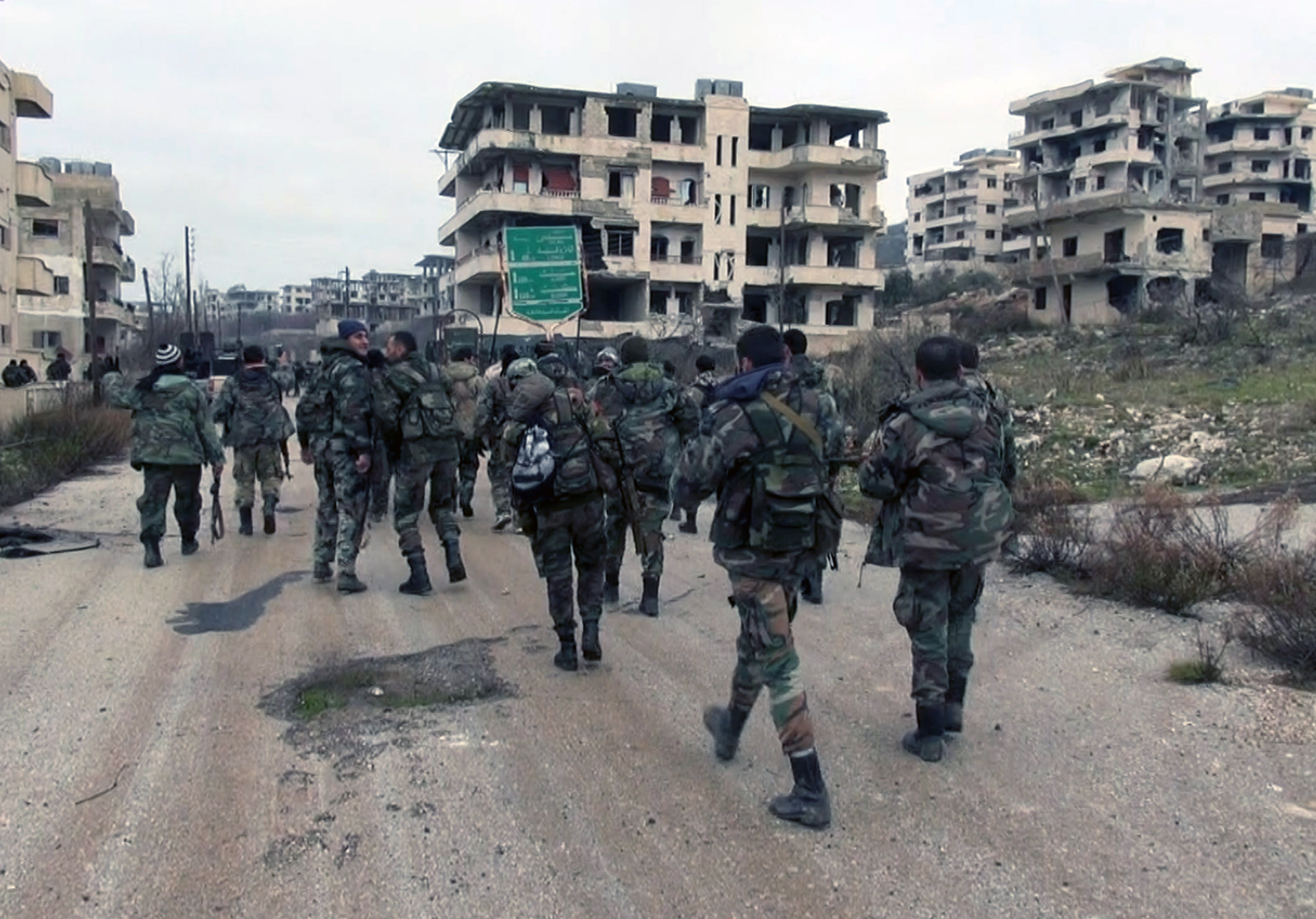 In this photo released on Tuesday, Jan 12, 2016, by the Syrian official news agency SANA, shows Syrian government troops and allied militiamen walk inside the key town of Salma in Latakia province, Syria