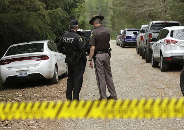Mason County Sheriff's Chief Criminal Deputies Russ Osterhout, left, and Ryan Spurling, right, stand on a road near the scene of a fatal shooting Friday, Feb. 26, 2016, near Belfair, Wash.